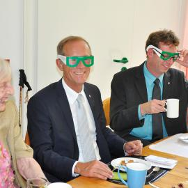 Frau Pfeifer, Staatsminister Wintermeyer und der Regionalbeauftragte für Mittelhessen Scherf (v.l.n.r.). Wintermeyer und Scherf tragen am Kaffeetisch Simulationsbrillen.