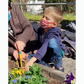Ein Kind bearbeitet das Beet mit einer Harcke