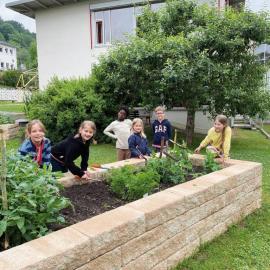 Kinder am vielfältig bepflanzten Hochbeet
