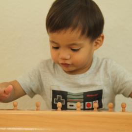 Ein Junge der Nest-Gruppe spielt mit dem Material