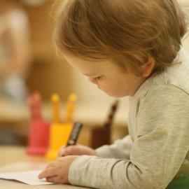 Ein kleines Mädchen malt konzentriert