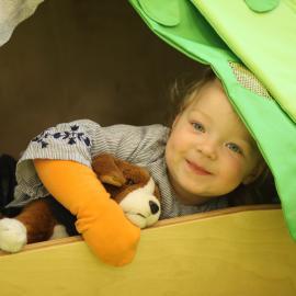 Ein Junge schaut aus einer Holzkiste