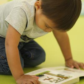 Ein Junge liest auf dem Boden kniend