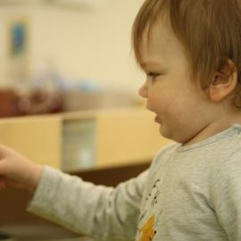Ein kleiner Junge schaut in ein Regal