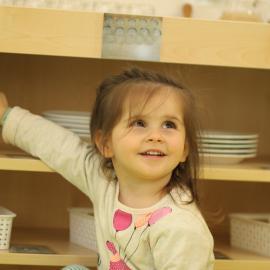 Ein Mädchen zeigt ins Regal