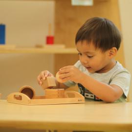 Ein Junge experimentiert mit Holzgegenständen