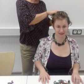 Die Dozentin steckt einer Teilnehmenden, die Halsketten ausprobiert, die Haare hoch