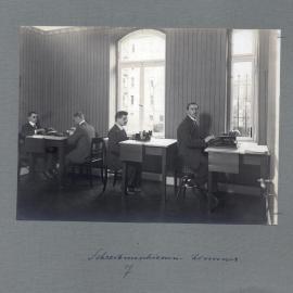 In einem Schreibmaschinenzimmer sitzen vier junge Männer bei der Arbeit