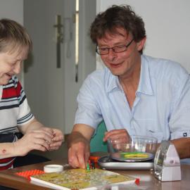 Der Seniorenberater zeigt einer Kundin Brettspiele