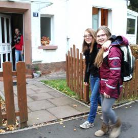 Zwei Internatsbewohnerinnen laufen lachend zum Eingang eines blista-Wohnhauses