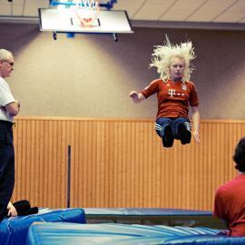blista Schüler beim Sportunterricht: Ein Mädchen springt auf eine Turnmatte