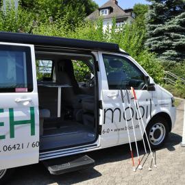 Der Kleinbus mit geöffneter Tür und Langstöcken
