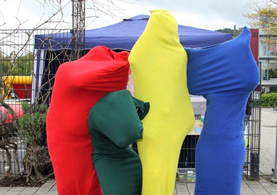 Bild 4 von 12: 4 Personen in bunten Ganzkörperkostümen