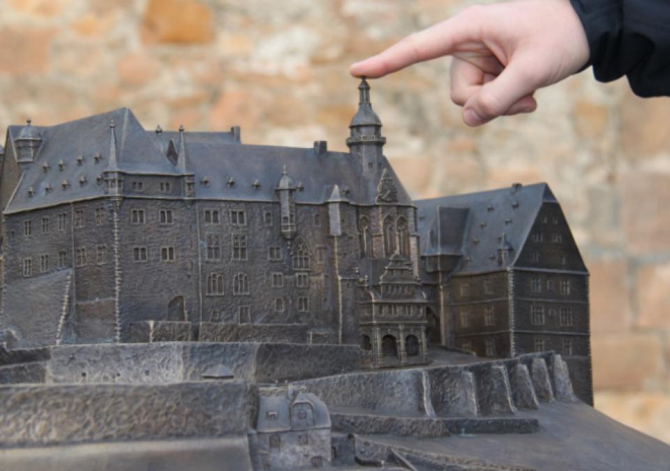Bild 1 von 12: Eine Hand zeigt mit dem Zeigefinger auf das taktile Marburger Schloss-Modell