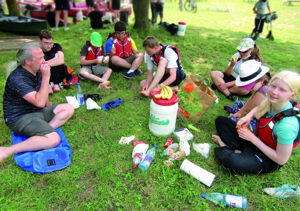 Bild 1 von 6: Foto einer Picknick-Szene auf der Wiese mit der wasserdichten Tonne in der Mitte und den Paddler*innen außenrum.