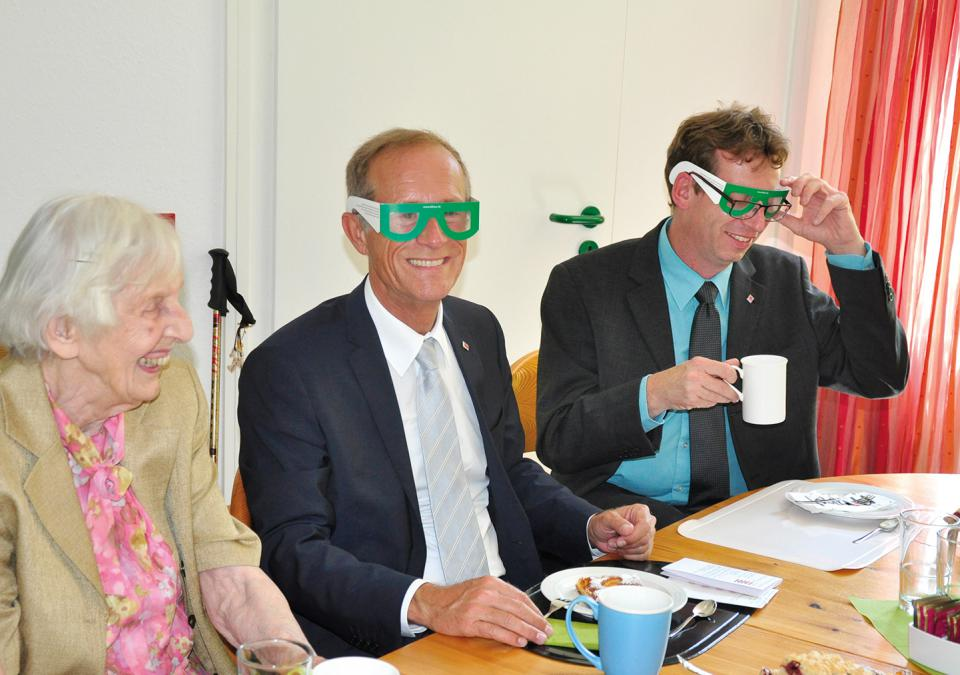 Bild 6 von 9: Frau Pfeifer, Staatsminister Wintermeyer und der Regionalbeauftragte für Mittelhessen Scherf (v.l.n.r.). Wintermeyer und Scherf tragen am Kaffeetisch Simulationsbrillen.