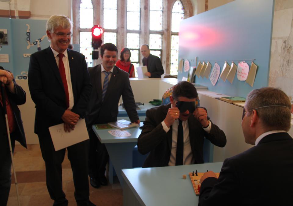 Bild 7 von 12: Staatsminister Boris Rhein und Oberbürgermeister Thomas Spies beim Menschärgere-dich-nicht-Spiel unter der Augenbinde
