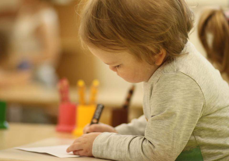 Bild 3 von 10: Ein kleines Mädchen malt konzentriert