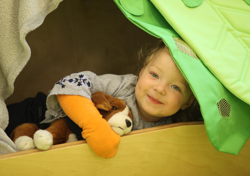 Bild 5 von 10: Ein Junge schaut aus einer Holzkiste