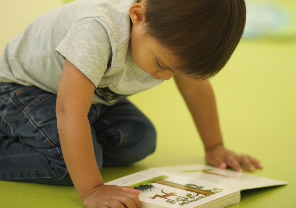 Bild 4 von 10: Ein Junge liest auf dem Boden kniend