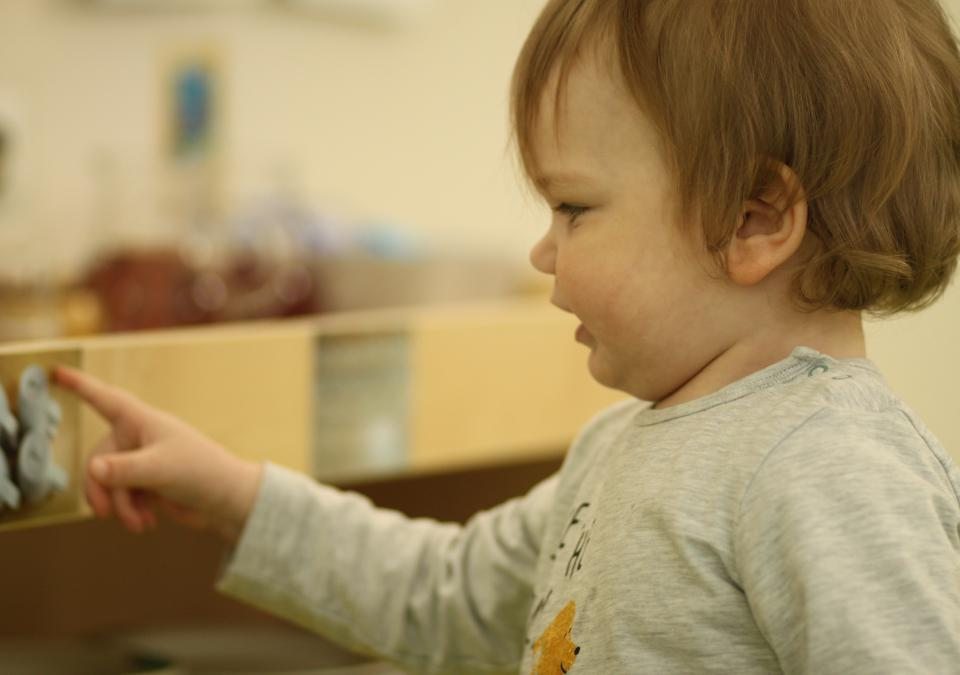 Bild 9 von 10: Ein kleiner Junge schaut in ein Regal