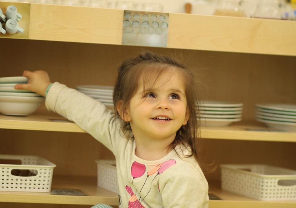Bild 6 von 10: Ein Mädchen zeigt ins Regal