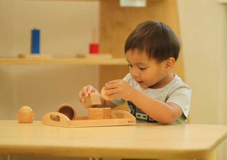 Bild 8 von 10: Ein Junge experimentiert mit Holzgegenständen