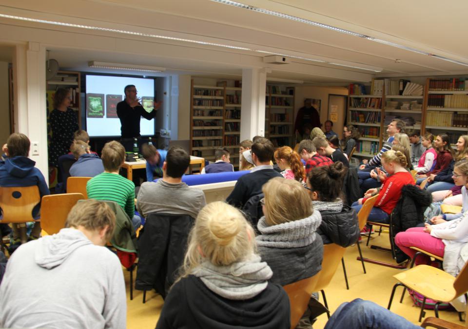Bild 11 von 12: In der Schülerbibliothek ist ein junges Auditorium aus der Montessori und der Carl-Strehl-Schuleversammelt