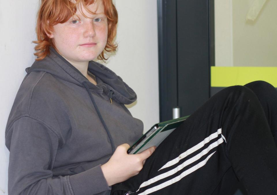 Bild 5 von 6: Ein Mädchen sitzt am Boden und schaut zu den Betrachtenden hin