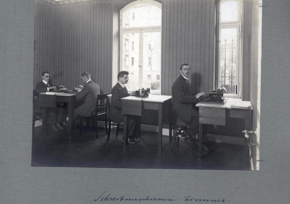 Bild 6 von 8: In einem Schreibmaschinenzimmer sitzen vier junge Männer bei der Arbeit