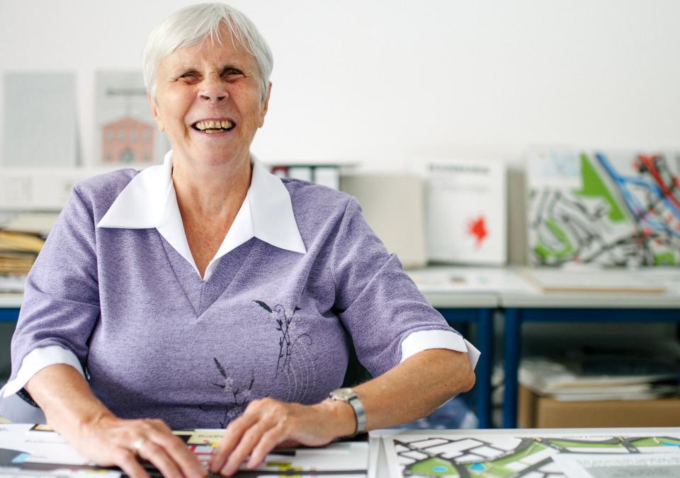 Bild 2 von 11: Eine Seniorin liest vergnügt in einem Stadtplan