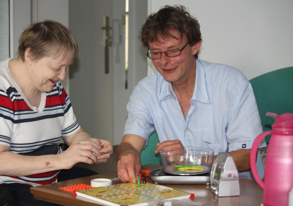 Bild 7 von 9: Der Seniorenberater zeigt einer Kundin Brettspiele