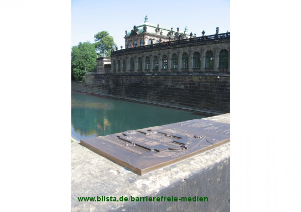 Bild 14 von 17: Grundrissmodell mit Punktschriftlegende installiert auf einem Sandstein-Brückengeländer, Bildhintergrund: Teile des Original-Zwingers