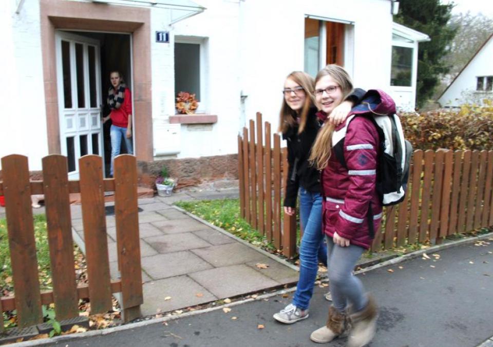 Bild 5 von 9: Zwei Internatsbewohnerinnen laufen lachend zum Eingang eines blista-Wohnhauses