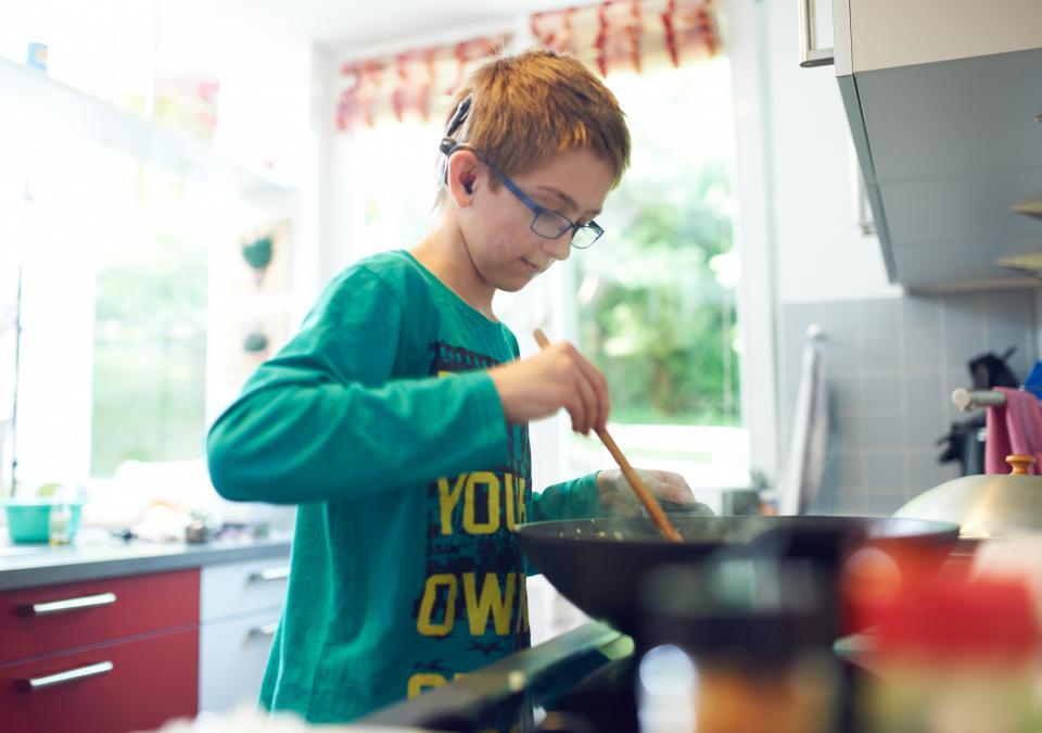 Bild 4 von 9: Ein Junge kocht
