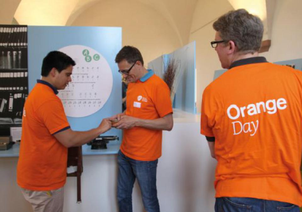 Bild 10 von 12: Im Rahmen des Orange Day unterstützte das Team der GSK Vaccines GmbH den Aufbau der Ausstellung