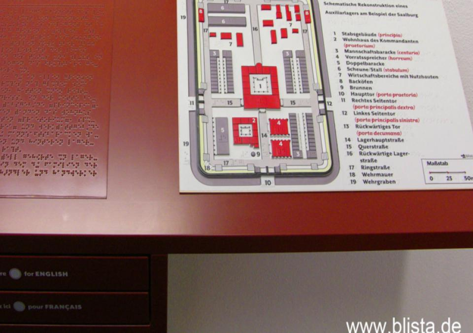 Bild 16 von 17: Aufteilung innerhalb eines Kastells mit nummerierten Erläuterungen in Legende, auf Tisch montiert, daneben Textplatte