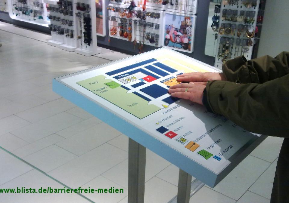 Bild 10 von 17: Tastende Hände an gerahmtem Modell mit Verkaufsständern im Hintergrund
