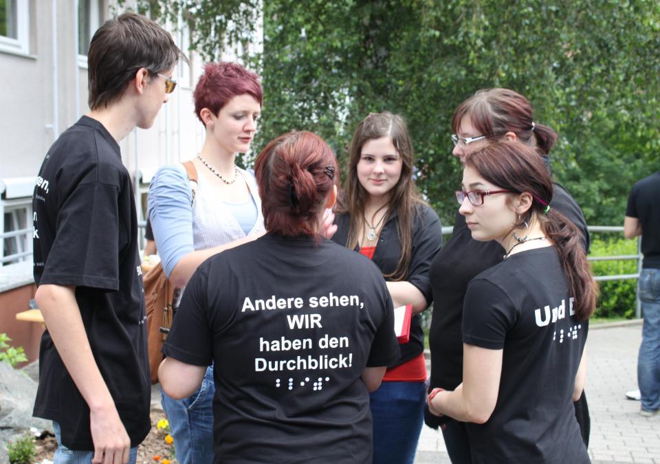 """Bild 5 von 11: Eine Gruppe von Schülern unterhält sich, auf einem T-Shirt ist """"Andere sehen, wir haben den Durchblick"""" zu lesen"""