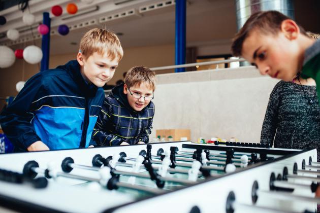 Kinder spielen am Tischkicker