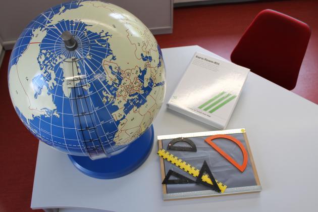 Das Foto zeigt einen Globus, ein Gallus-Zeichenbrett und ein Buch