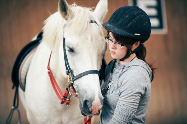 Eine Schülerin führt ihr Reitpferd