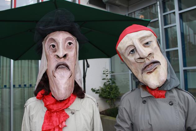 Zwei Theatermacher tragen imposante Gesichtsmasken zur Schau
