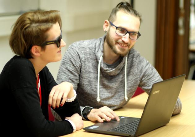 Eine junge Frau und ein junger Mann arbeiten am Laptop