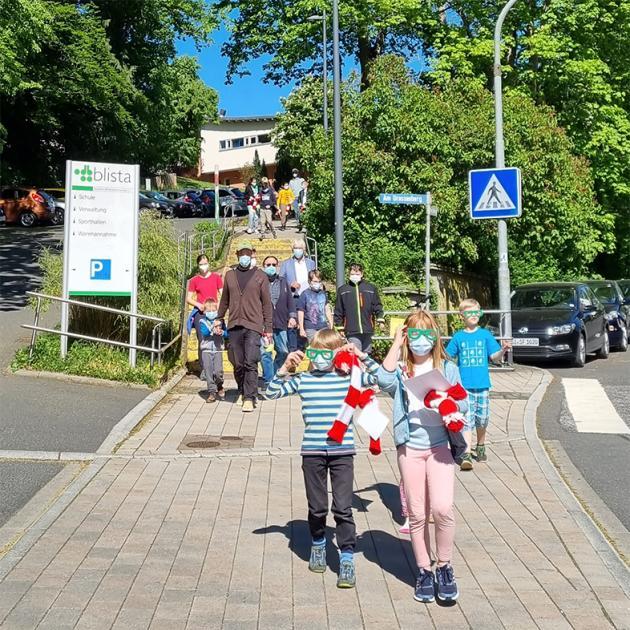 Drei Kinder mit Simulationsbrillen, zwei ausgerüstet mit den gestrickten Pollermützen und den Erklärungsschildern vorneweg auf dem Weg zur Aktion.