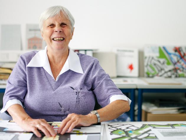 Eine Seniorin liest vergnügt in einem Stadtplan