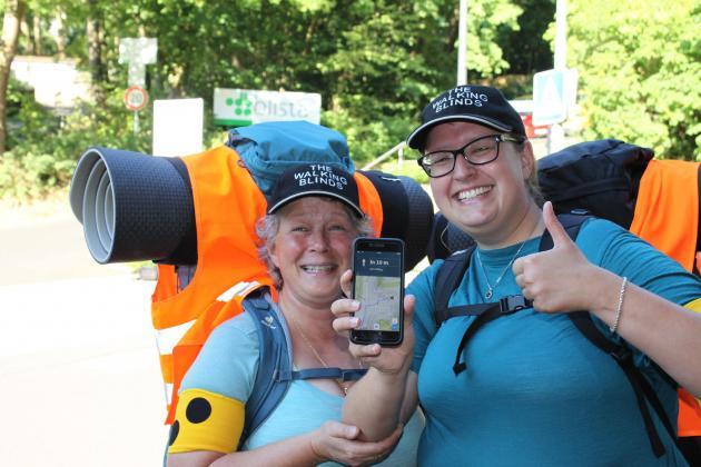 Zwei vergnügte Frauen mit Rucksäcken und Smartphone