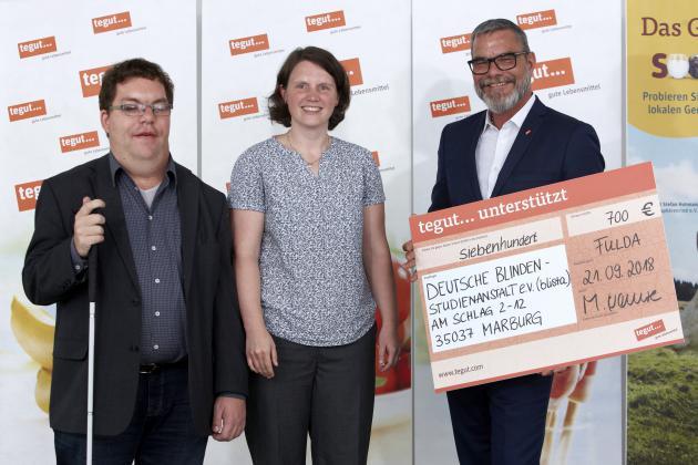 3 Personen mit einem Großbild des Schecks