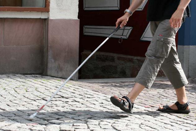 Mann läuft mit Langstock eine Straße entlang. Man sieht nur die Beine.