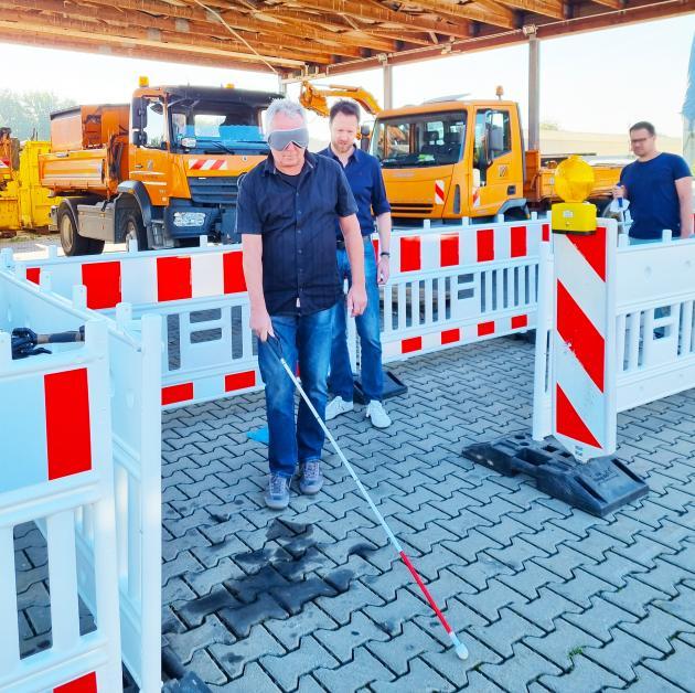 Ein Mann tastet sich mit dem Langstock durch eine Baustellenführung
